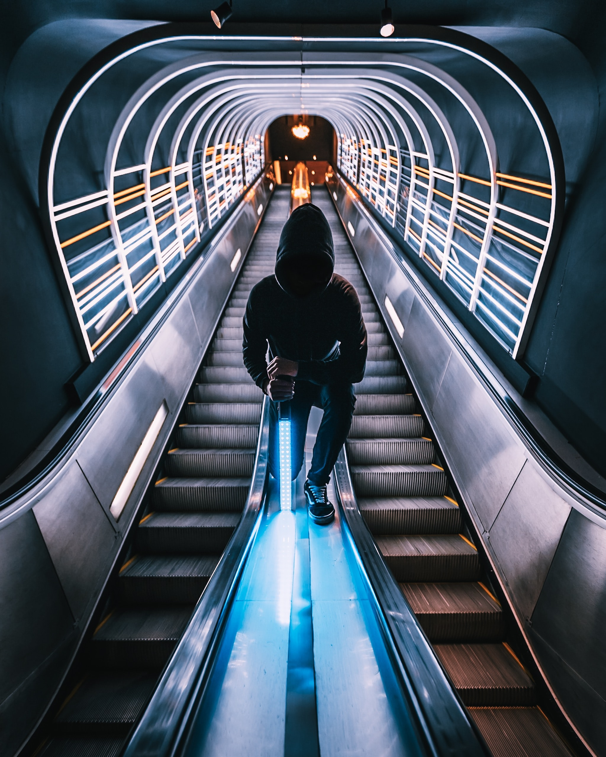 person standing between escalators