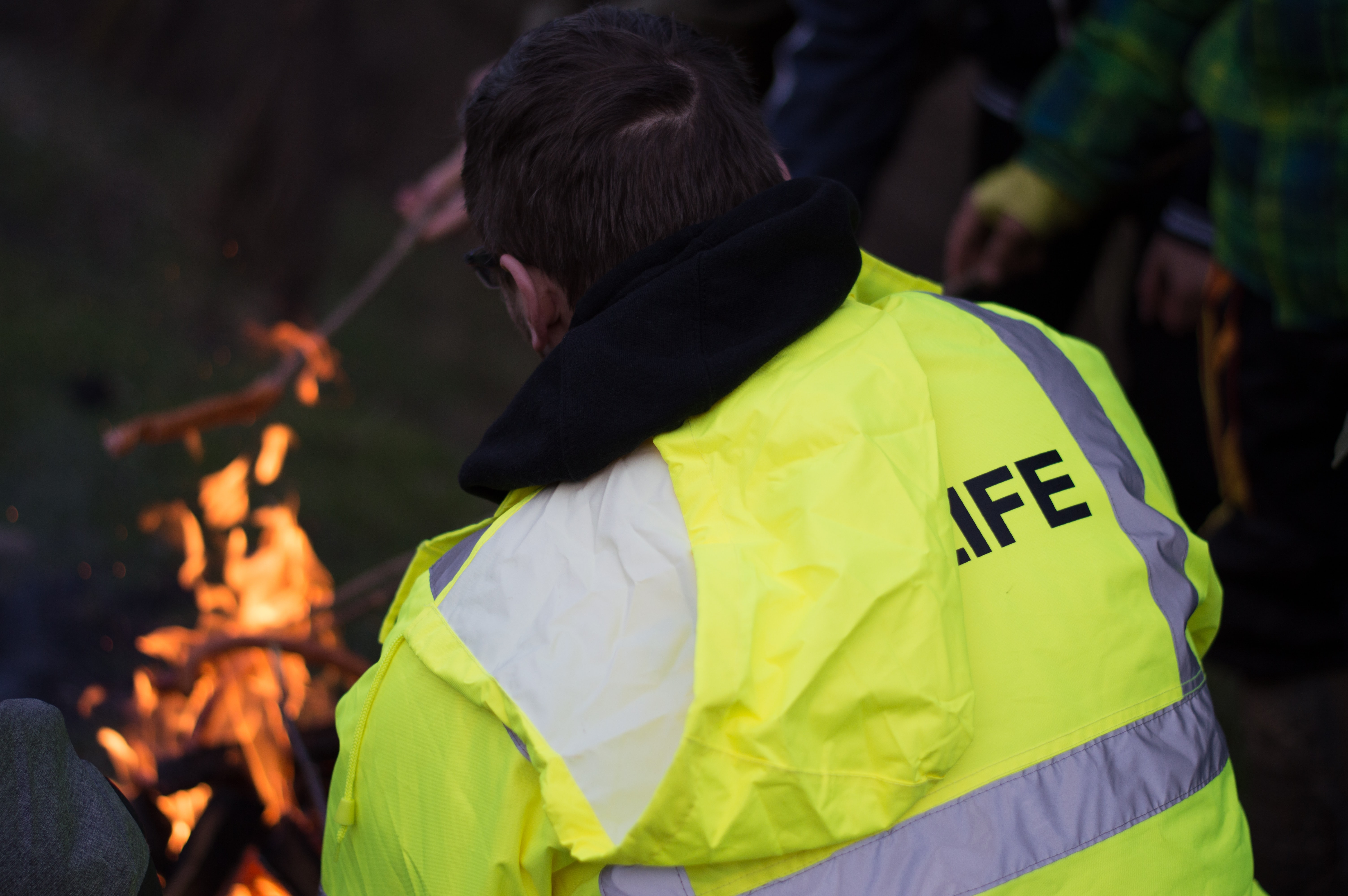 person wearing yellow and gray high visibility vest