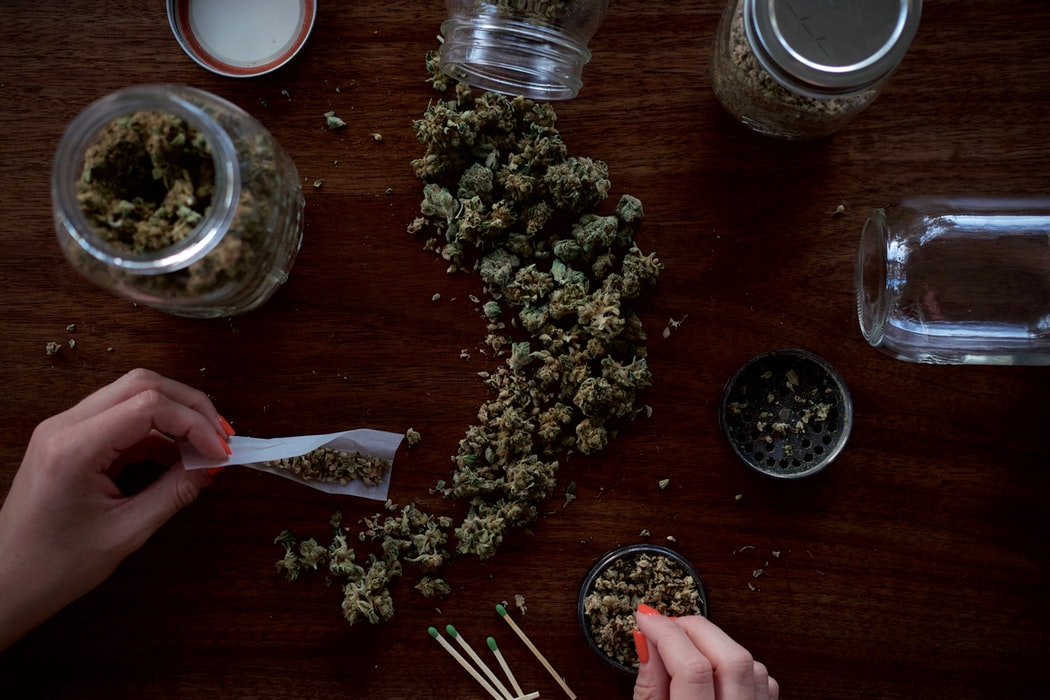 a table is covered with bits of marijuana as a woman rolls some in paper