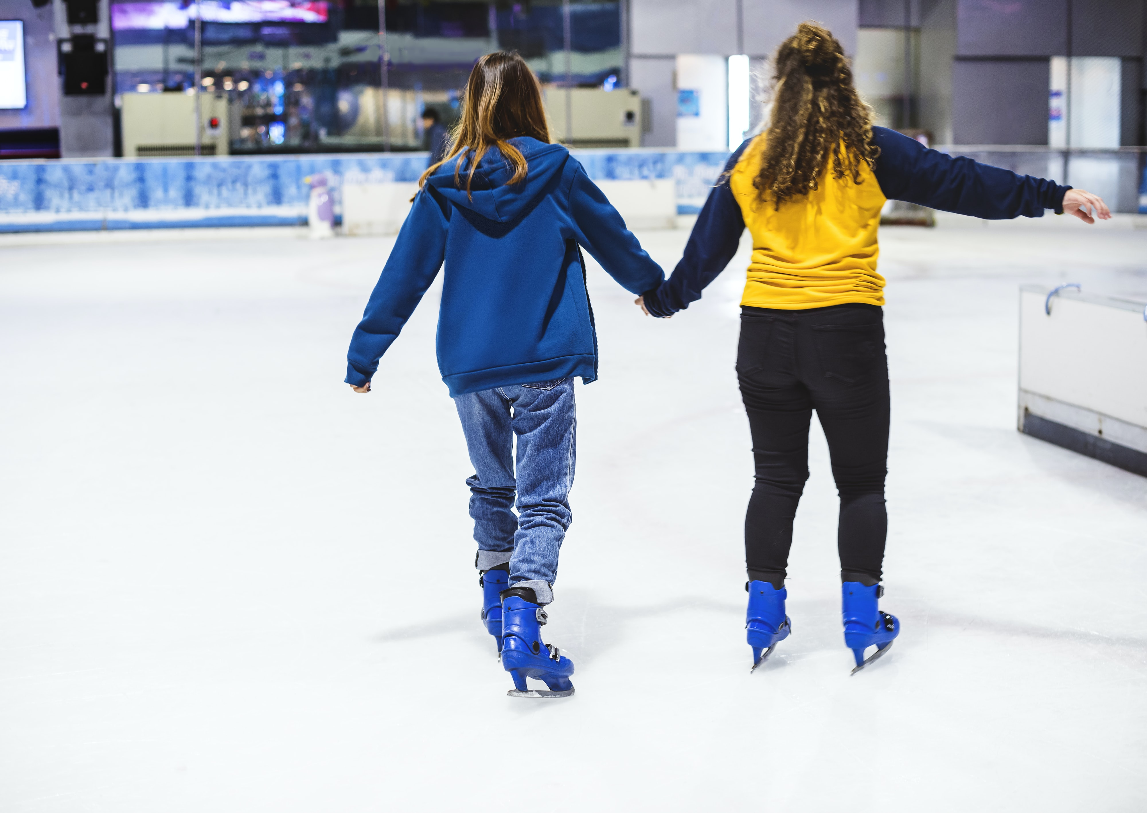 two women holding hands together while ice skating