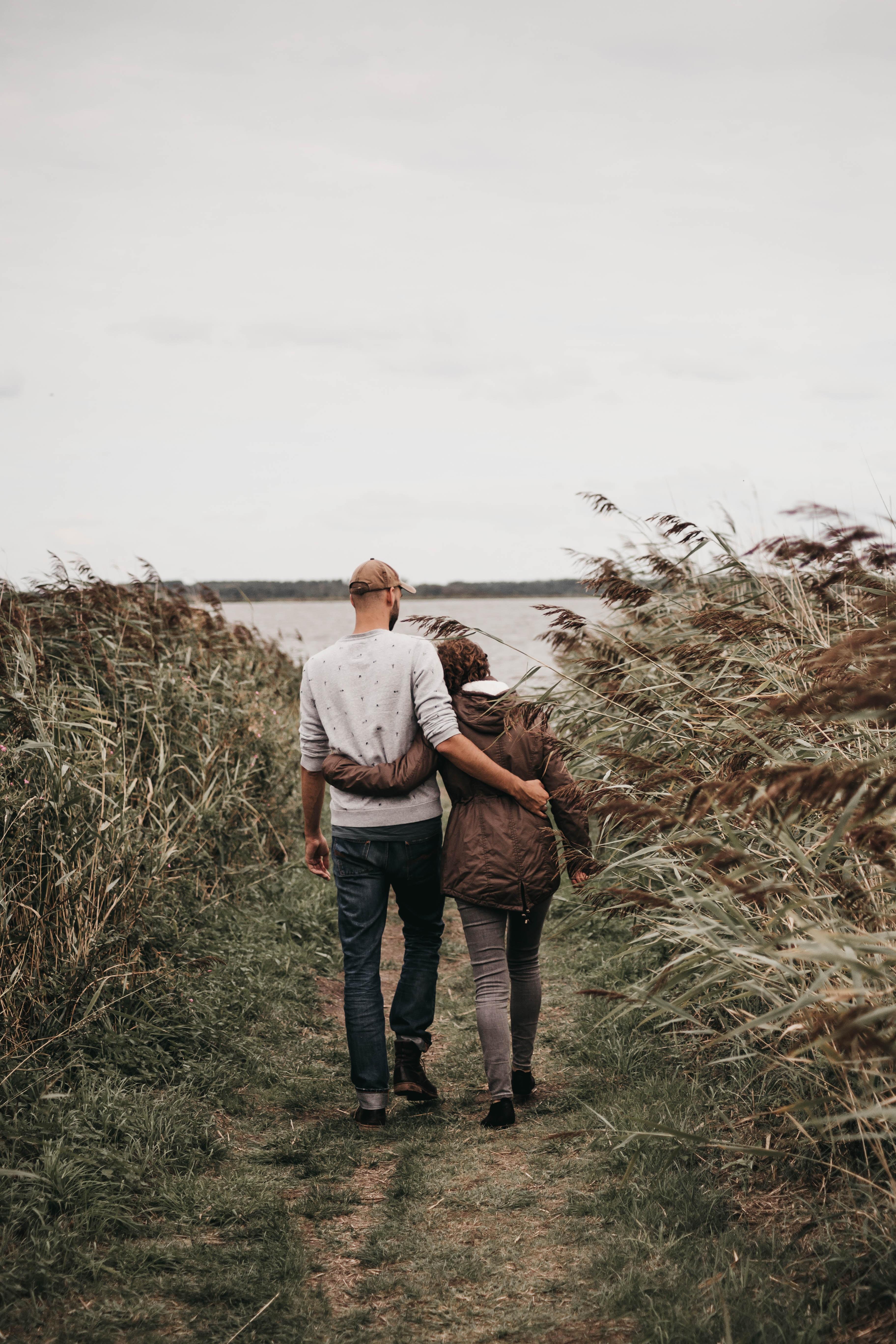 man hugging woman while walking