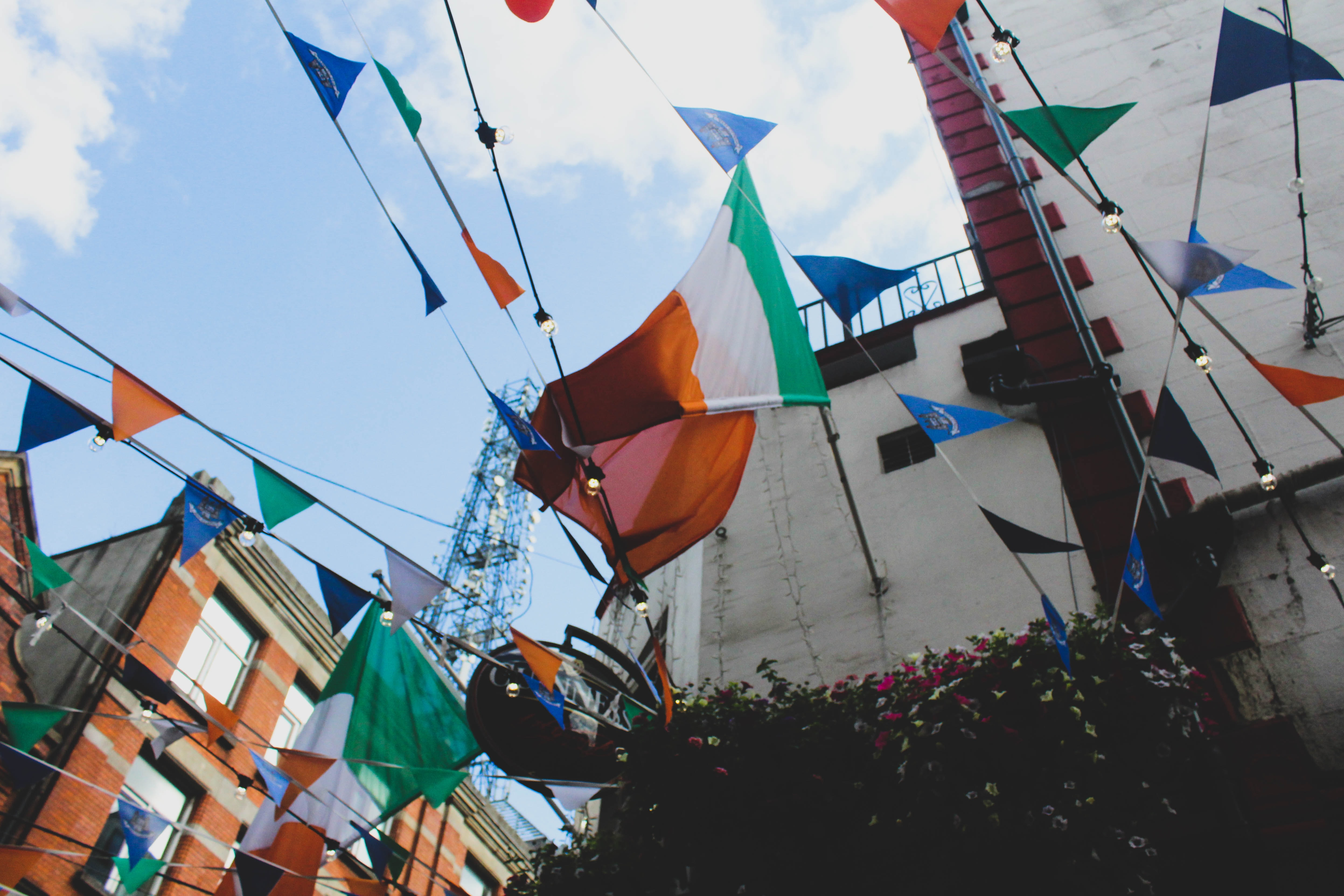 multicolored bunting with stripe flag hang near buildings