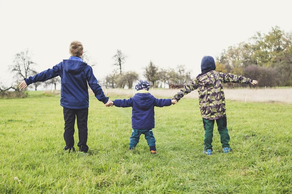 three children holding hands standing on grasses