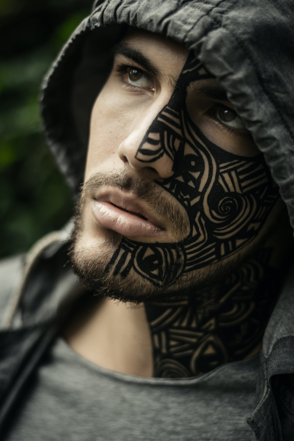 man with face tattoo wearing gray hoodie