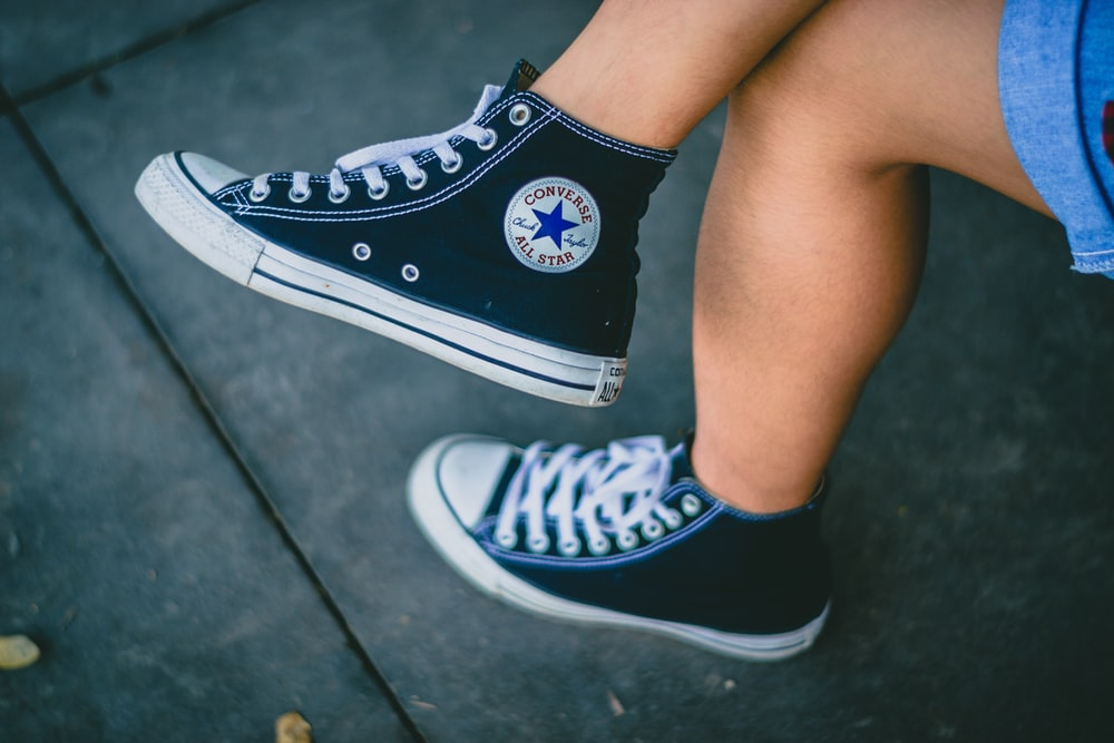 person wearing black Converse All-star sneakers