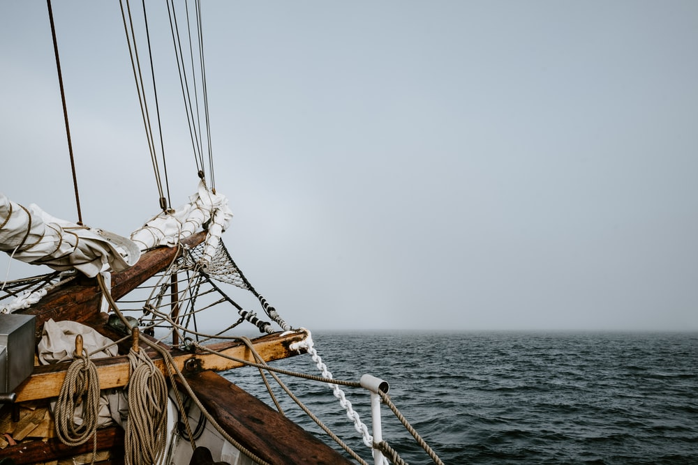 brown sailboat on body of water