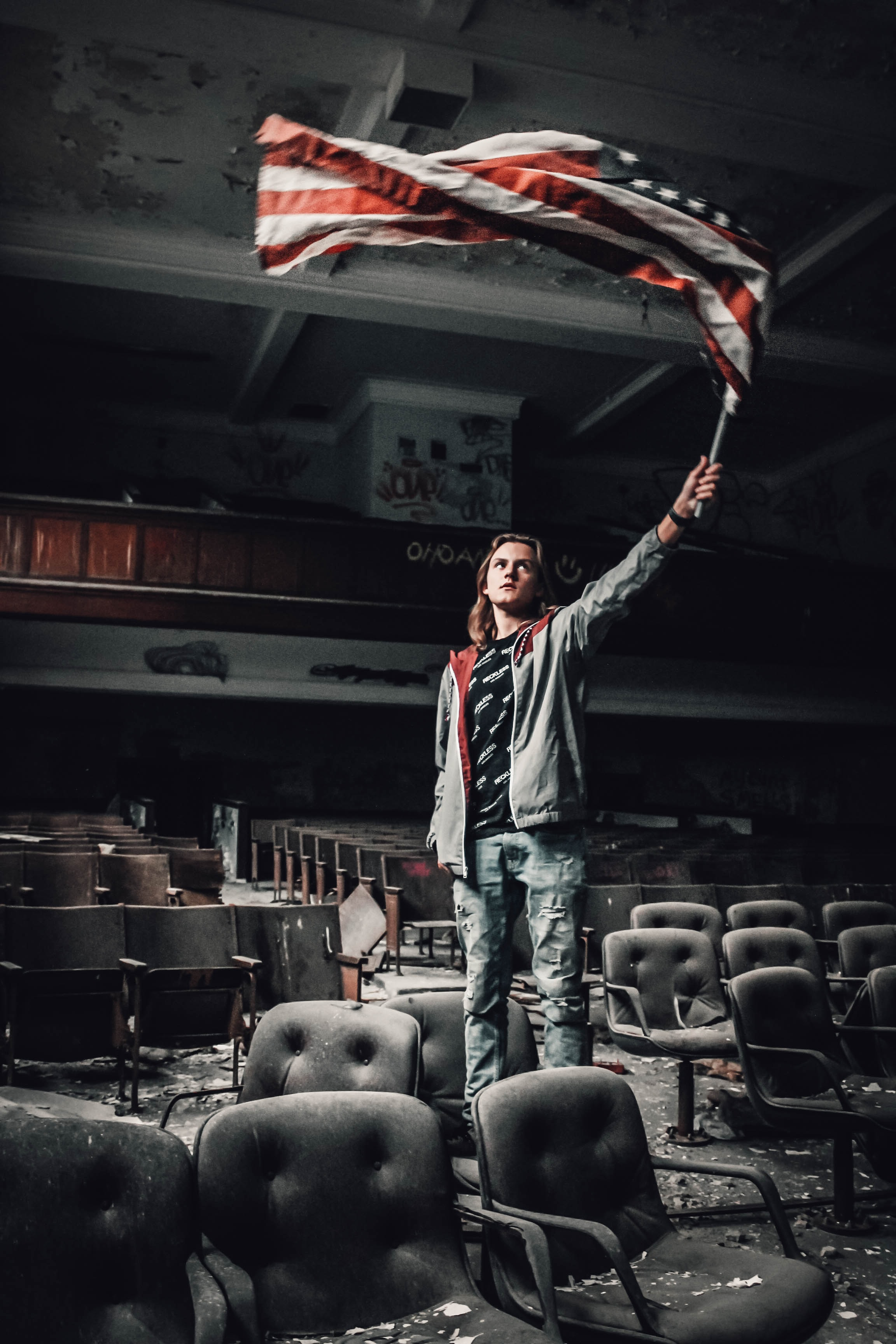 man rising US flag inside theater