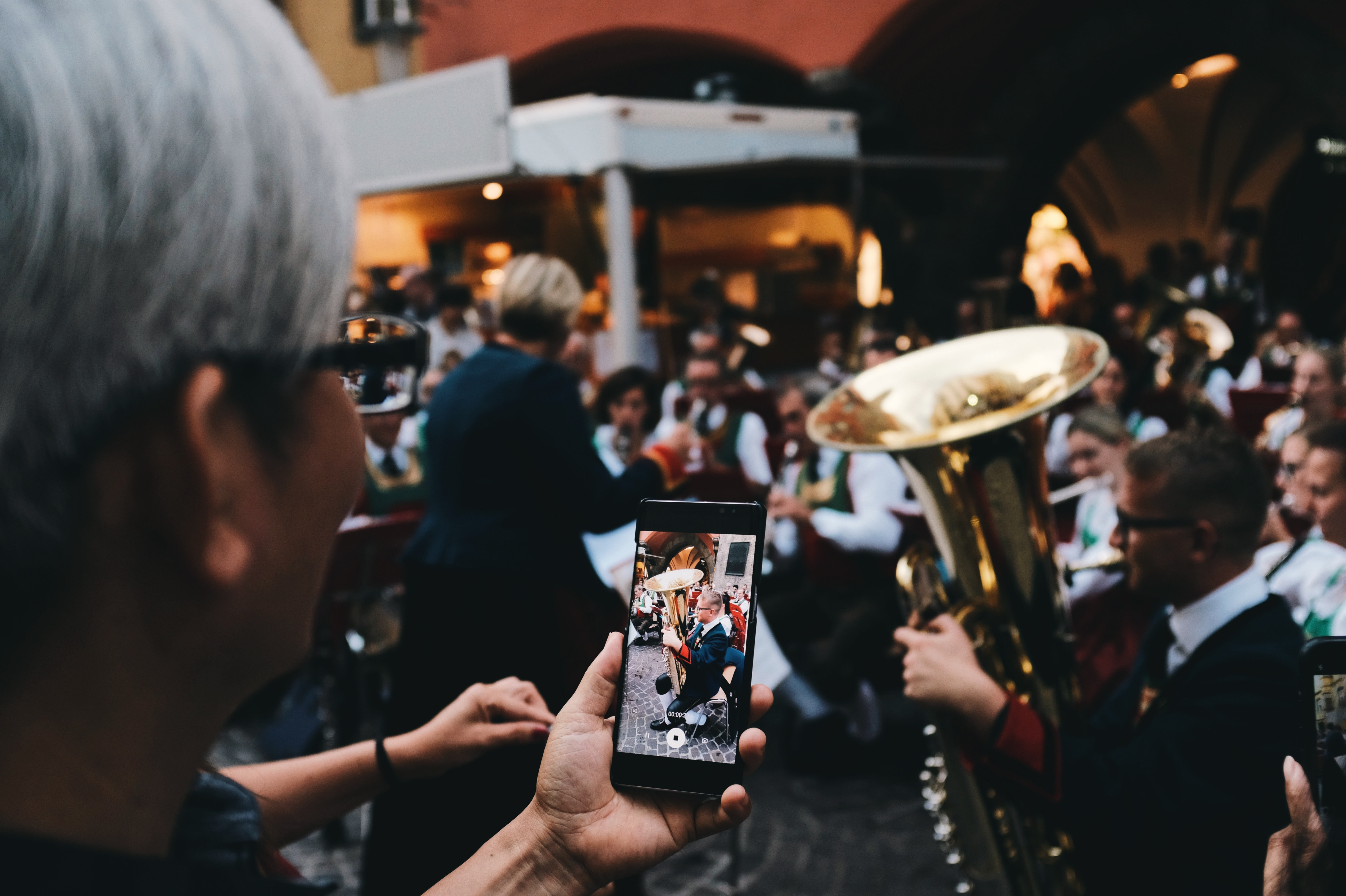 selective focus photo of woman holding phone taking a photo of man playing instrument