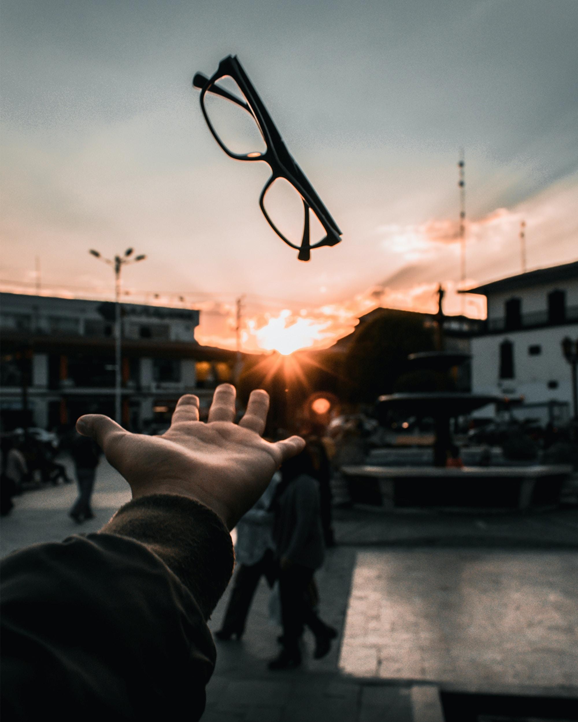 person catching black framed eyeglasses at golden hour