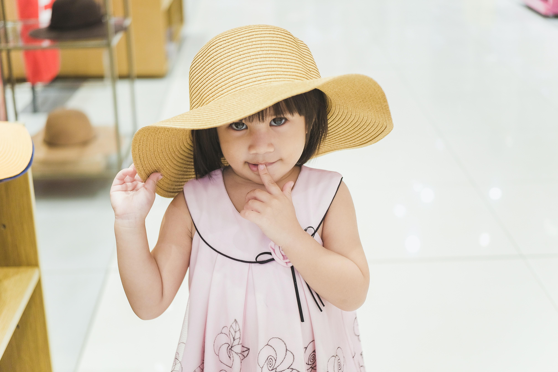 girl wearing brown sun hat and pink sleeveless dress