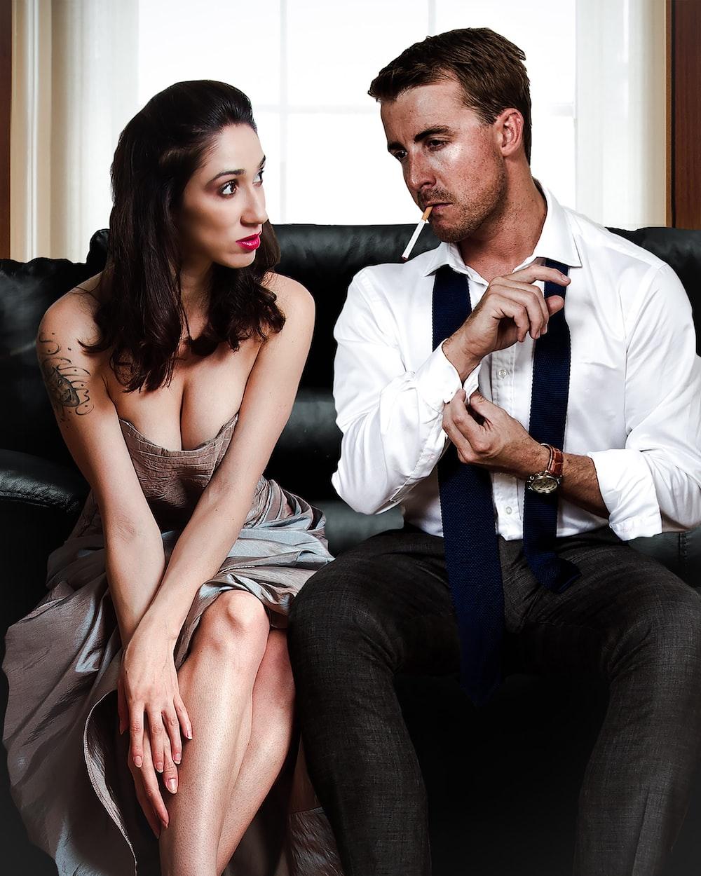 man sitting on sofa beside woman