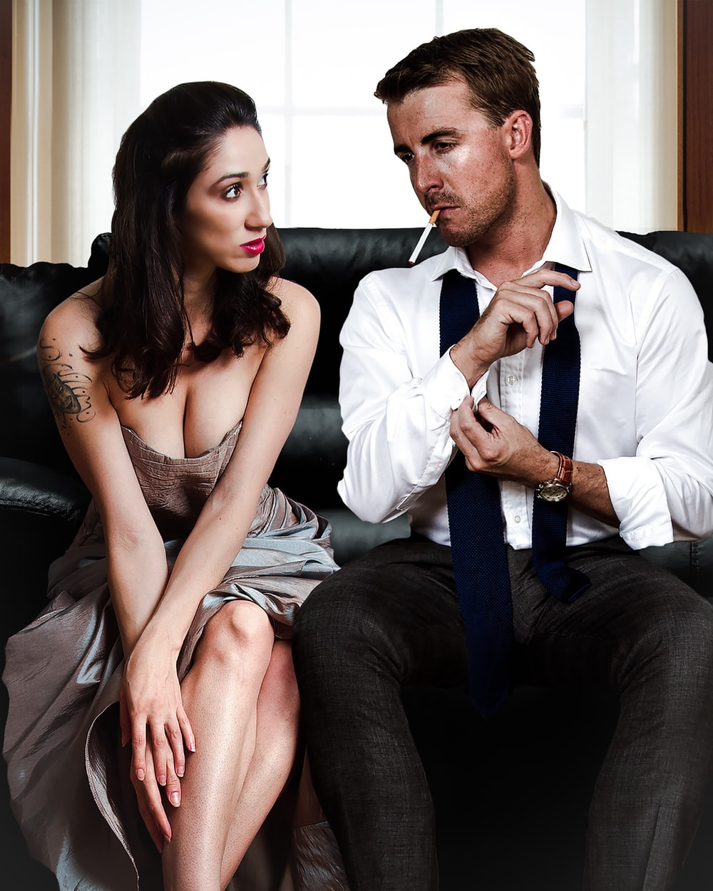 man sitting on sofa beside woman