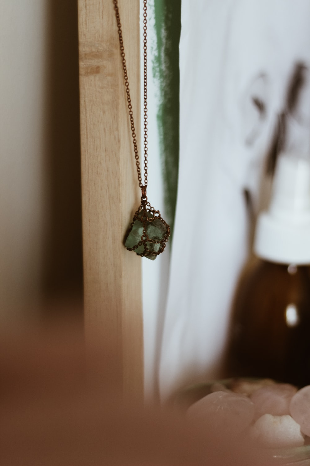 silver-colored necklace hanging on white wooden wall