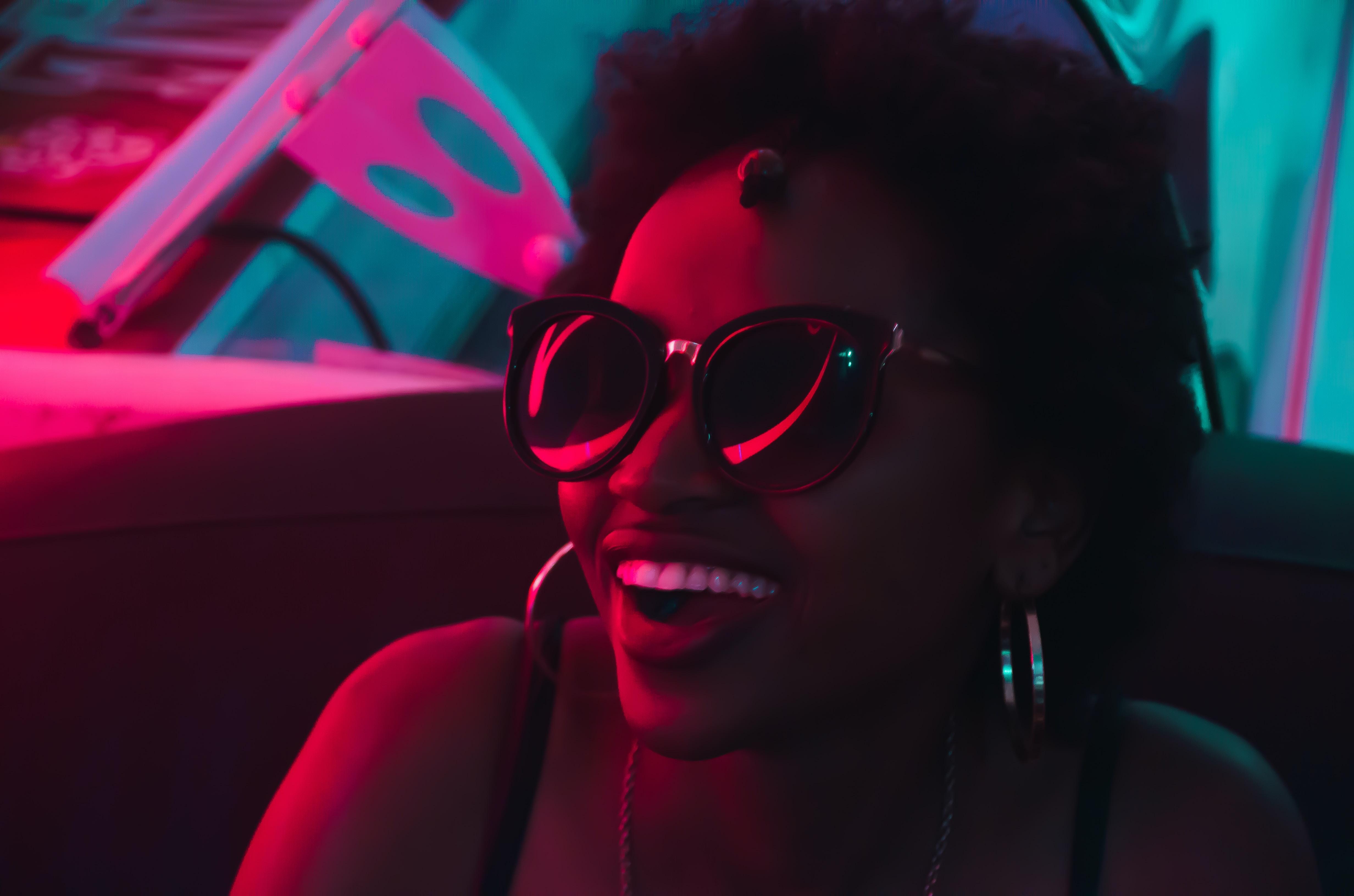 smiling woman wearing black sunglasses and hoop earrings