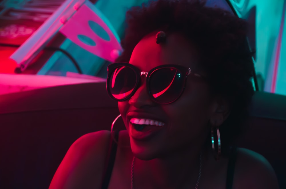 smiling woman wearing black sunglasses and hoop earrings