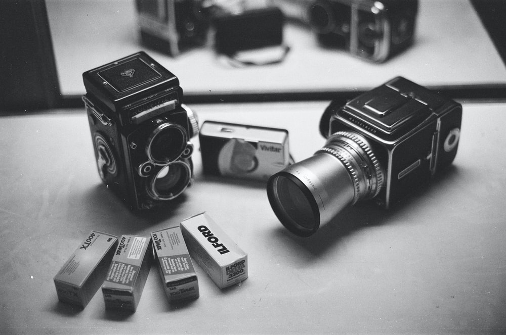black and silver cameras in grayscale photography