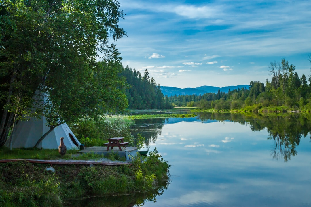 This peaceful spot is located on Sand Creek,  in Sandpoint, Idaho.   I often walked on a public trail past this spot but never saw anyone out enjoying the view  at that picnic table.
