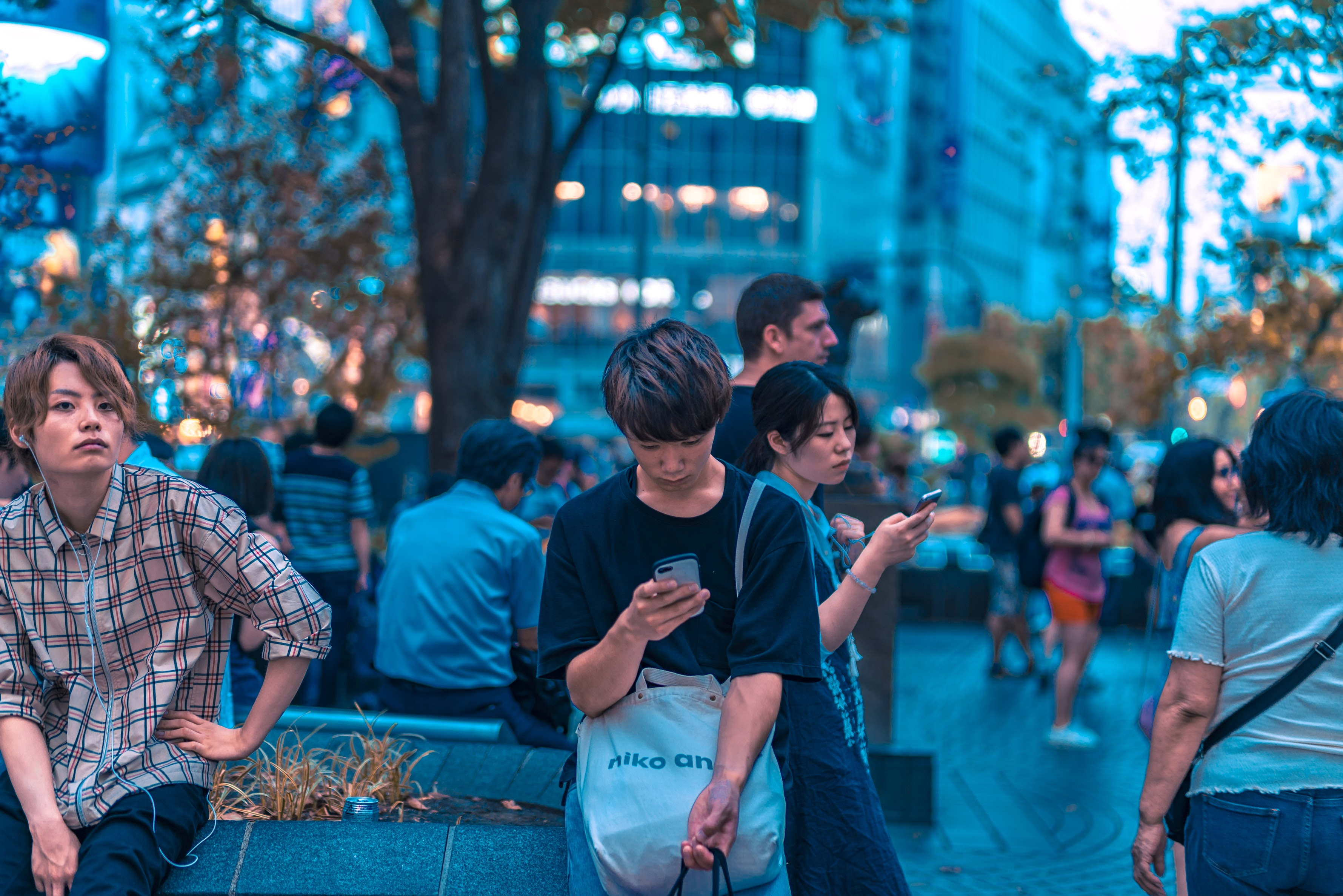 selective focus photography of man sitting on concrete chair while holding smartphone