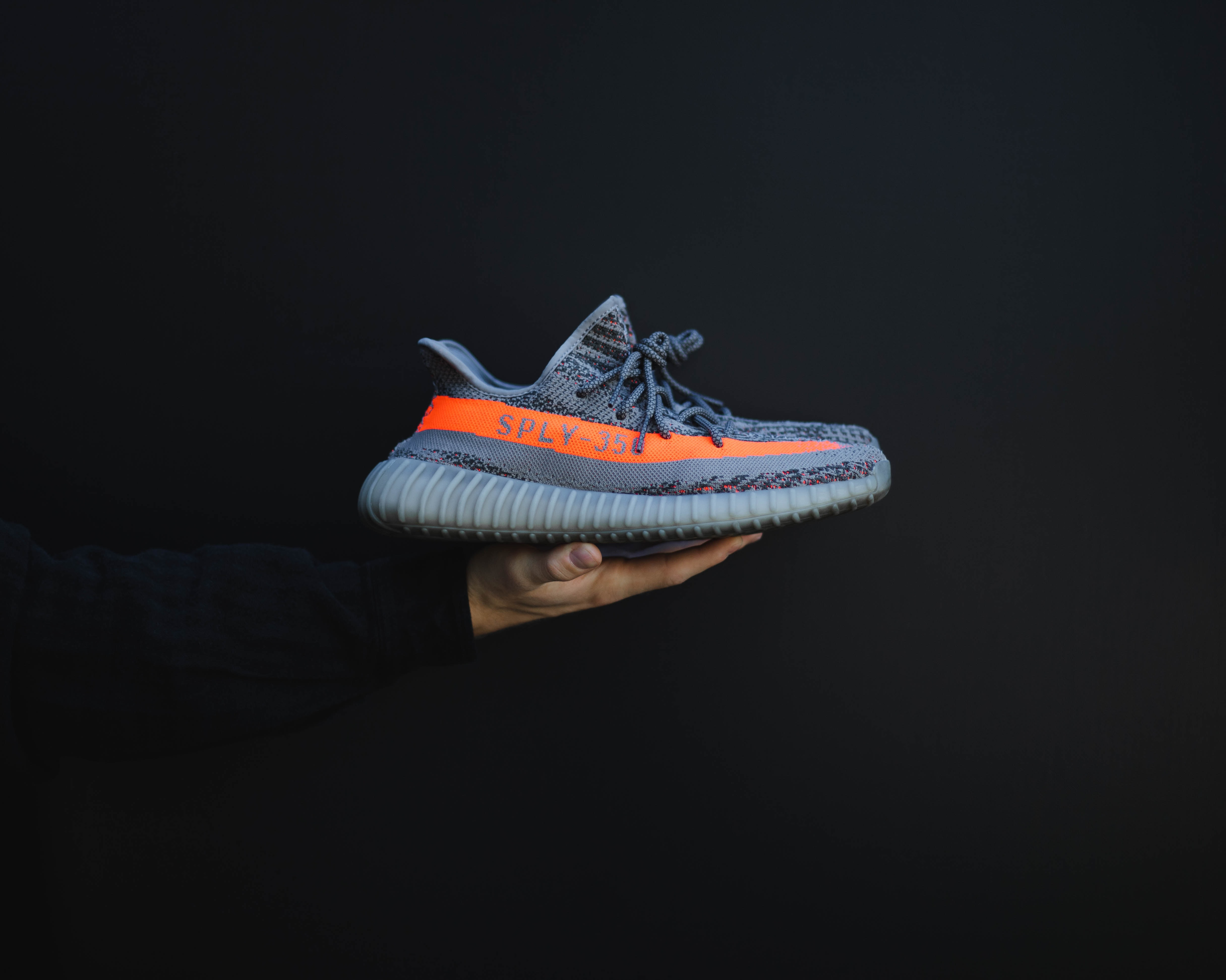 person holding gray and orange adidas Yeezy Boost 350 V2