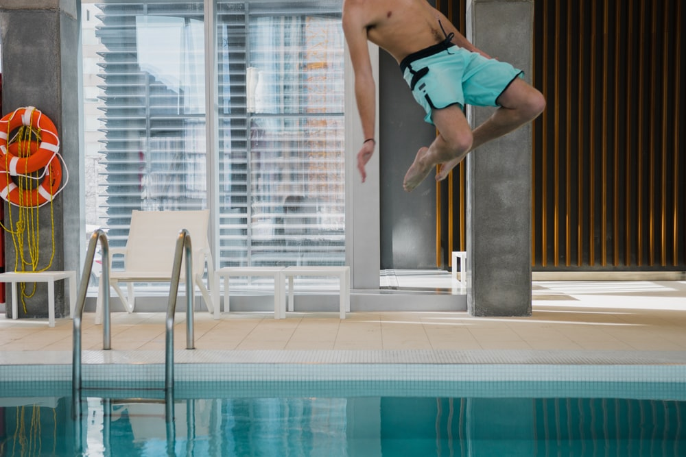 man in teal boardshorts jumping on pool
