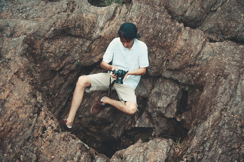 person holding DSLR camera sitting on brown rock