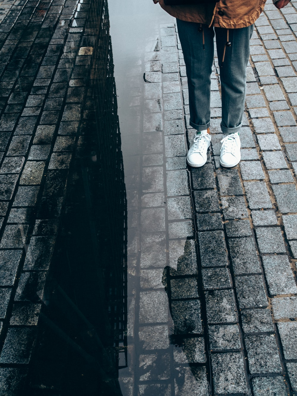 person wearing pair of white low-top sneakers