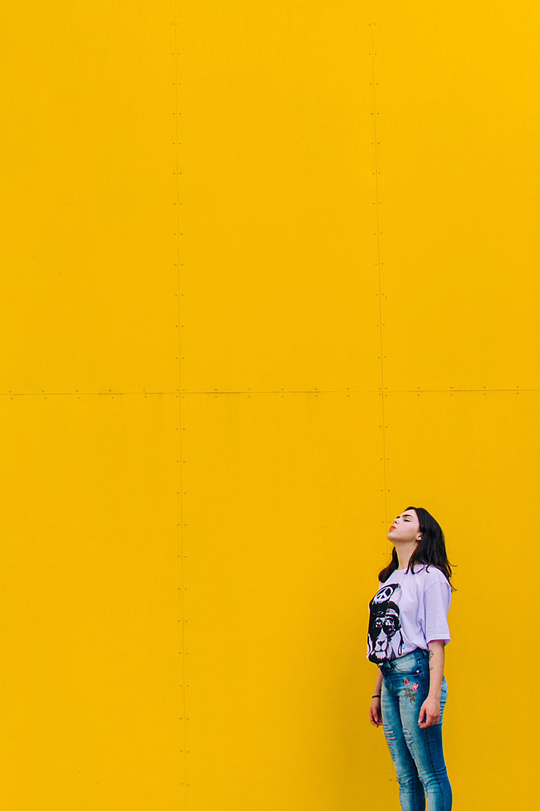 woman in purple shirt standing beside yellow wall