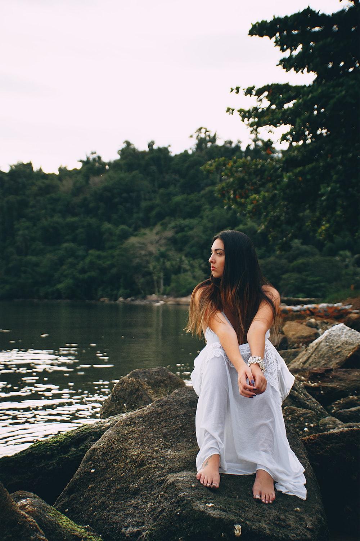 woman sitting on rock beside water