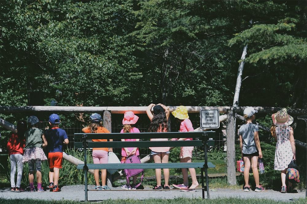 children standing beside fence during daytime