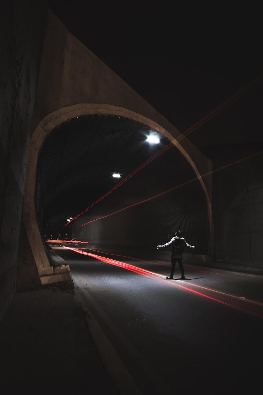 person near gray concrete tunnel