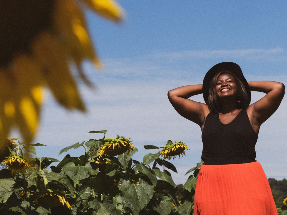 woman in black tank top in sunflower field during daytime