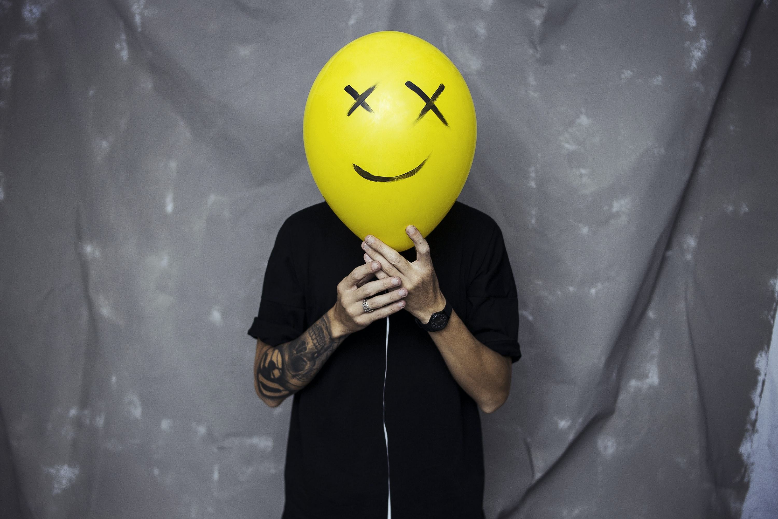 person wearing black shirt holding yellow and black balloon