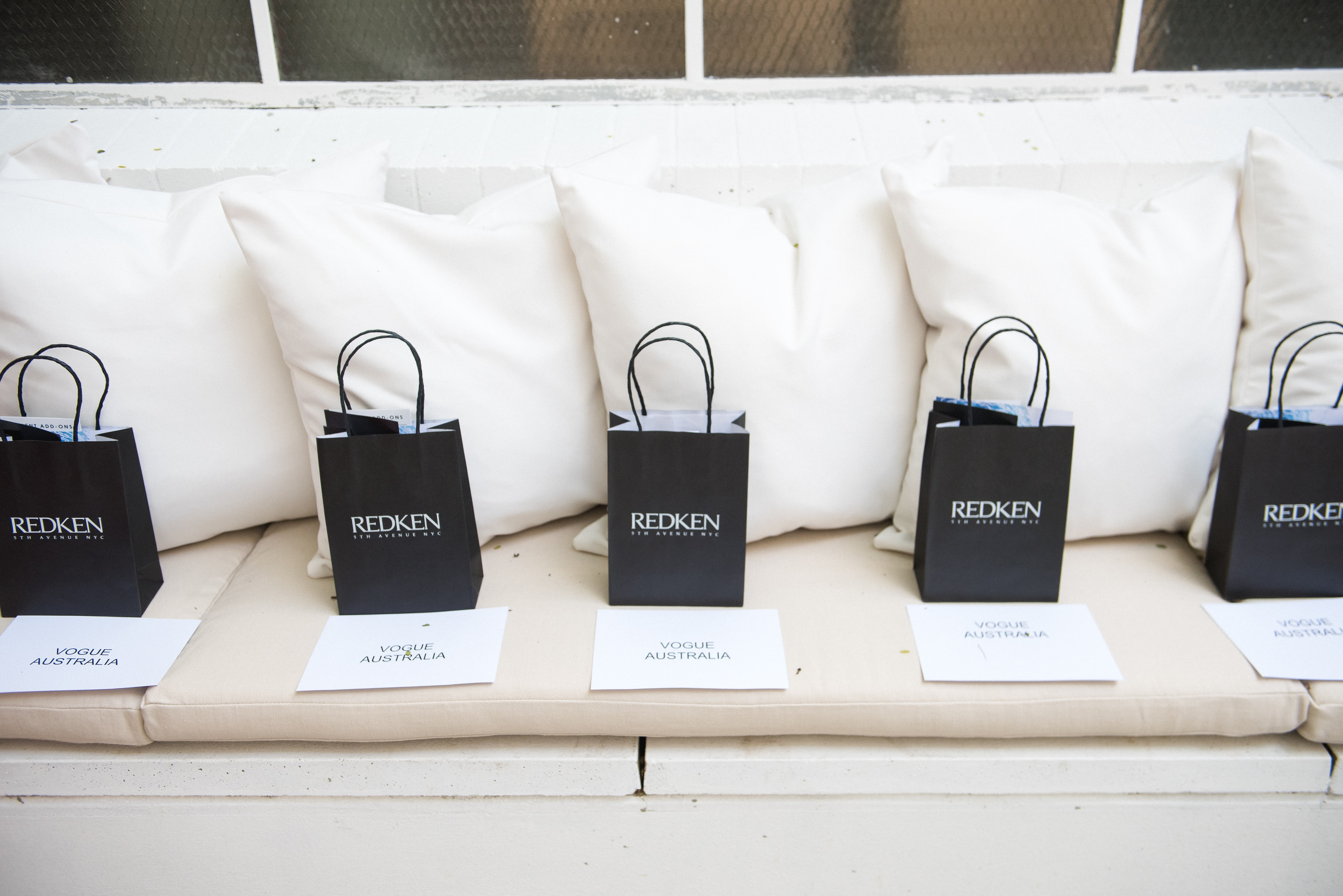 five black paper bags on top gray padded sofa