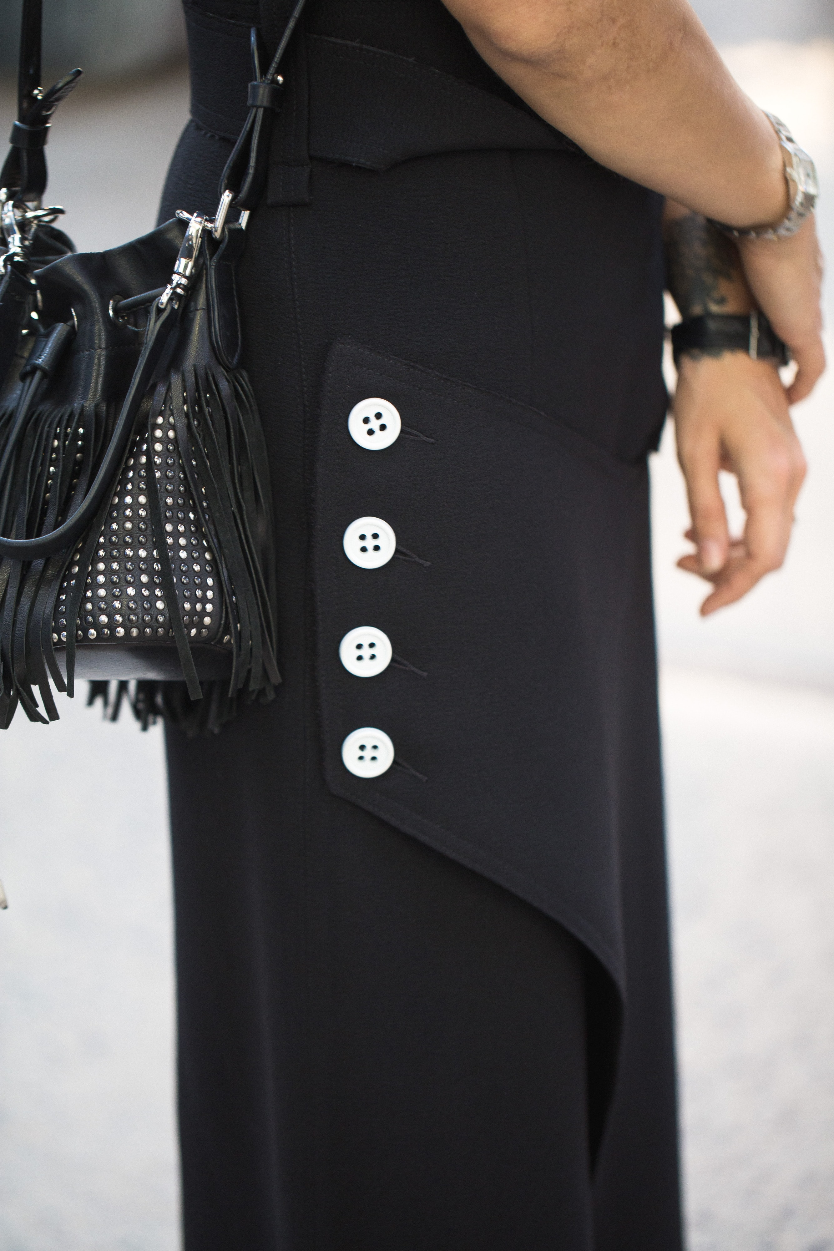 woman in black dress and crossbody bag with fringe