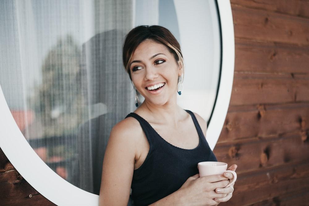 woman wearing black tank top holding mug