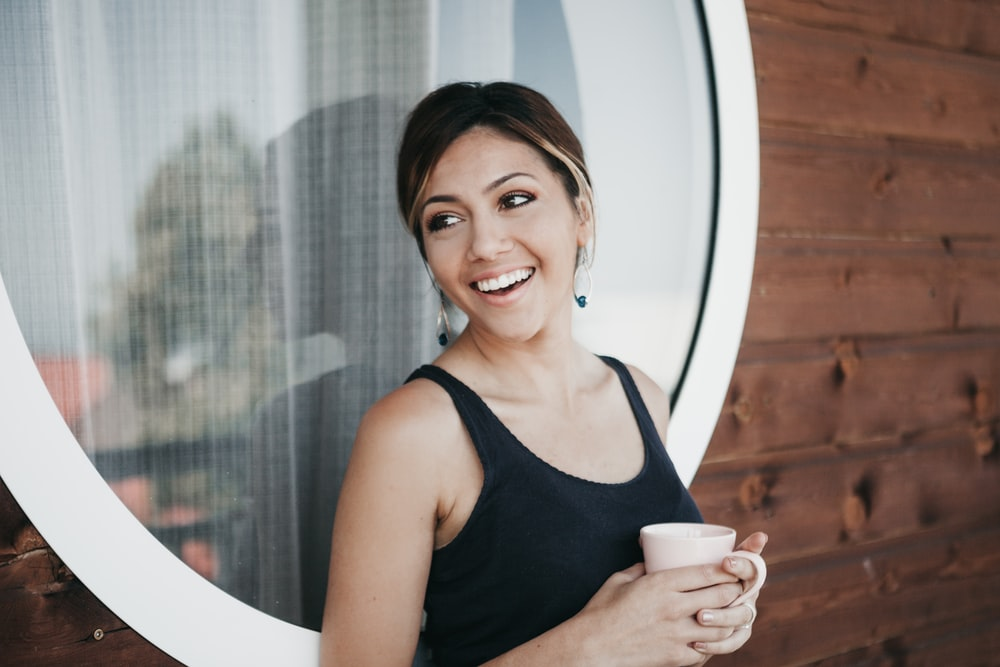 woman wearing black tank top holding mug