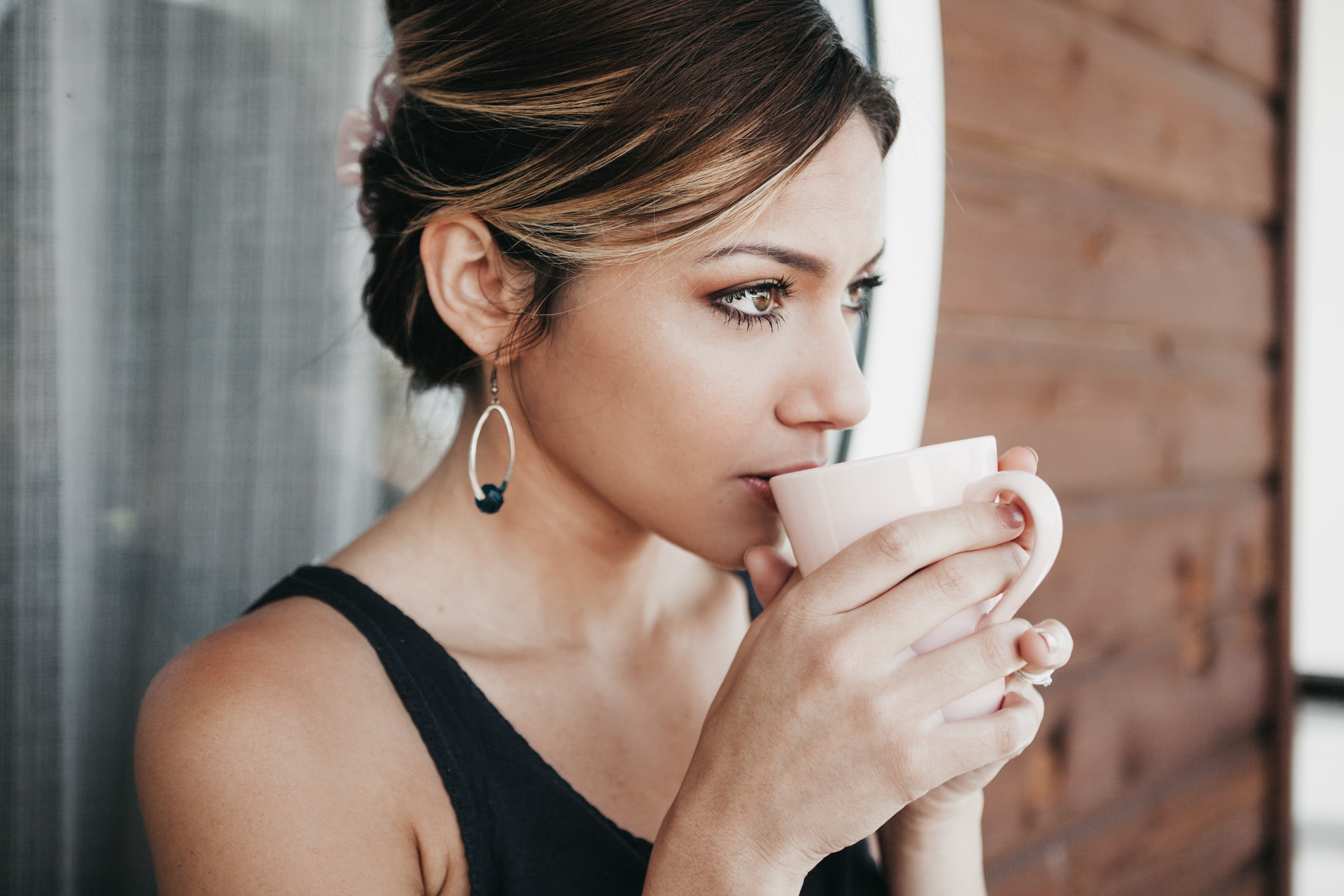 woman leaning on wall drinking coffee