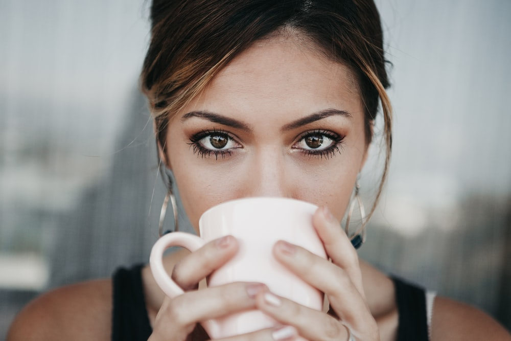 woman drinking from white coffee cup