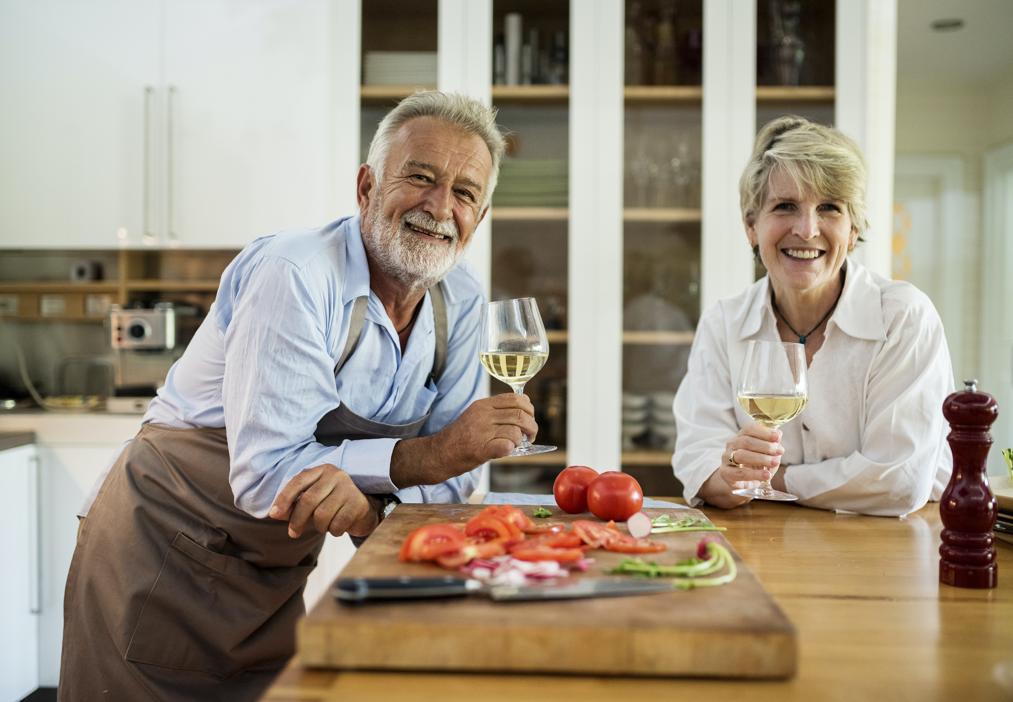 man and woman holding wine glasses smiling in front of table