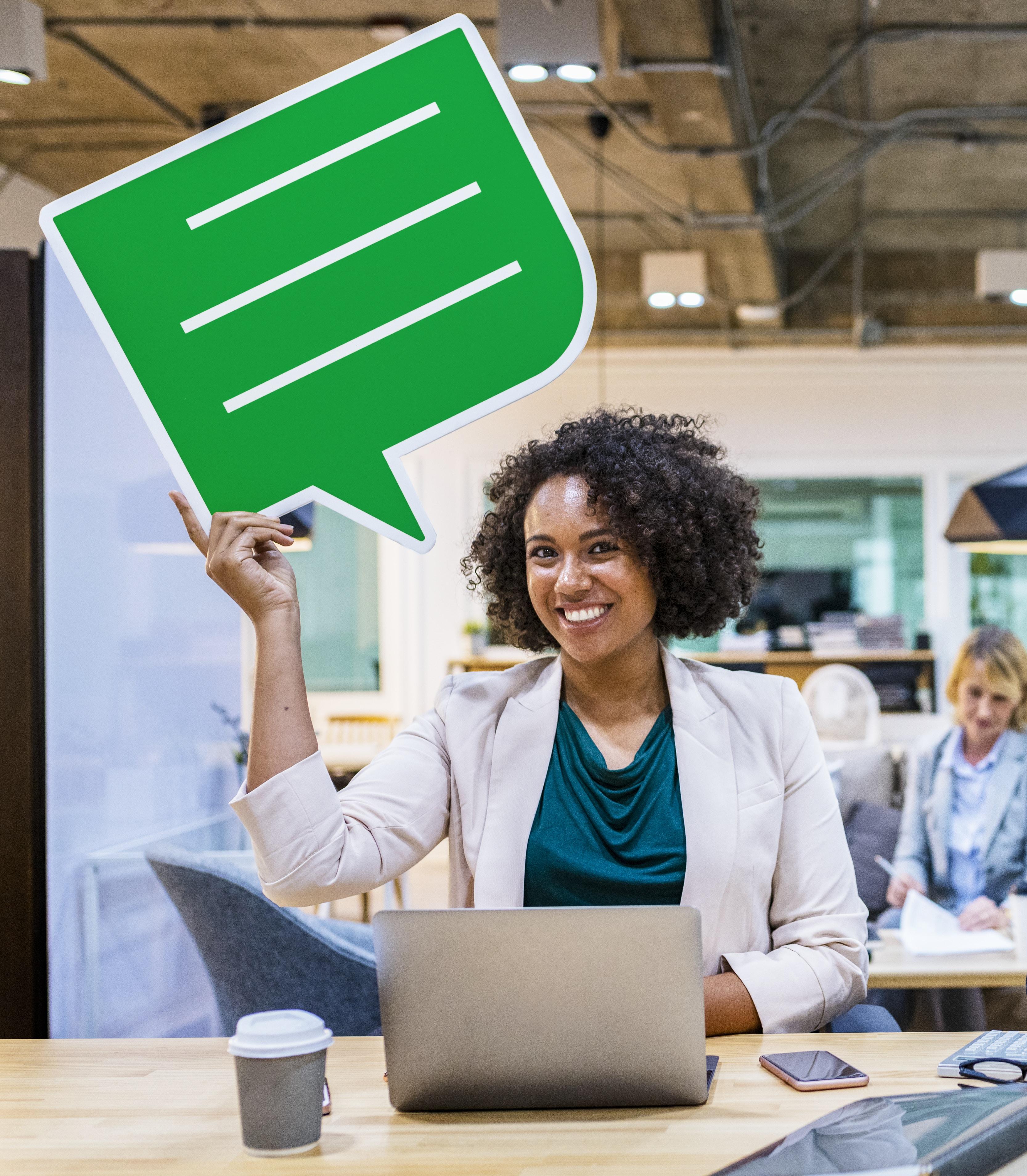 woman sitting holding green dialogue box