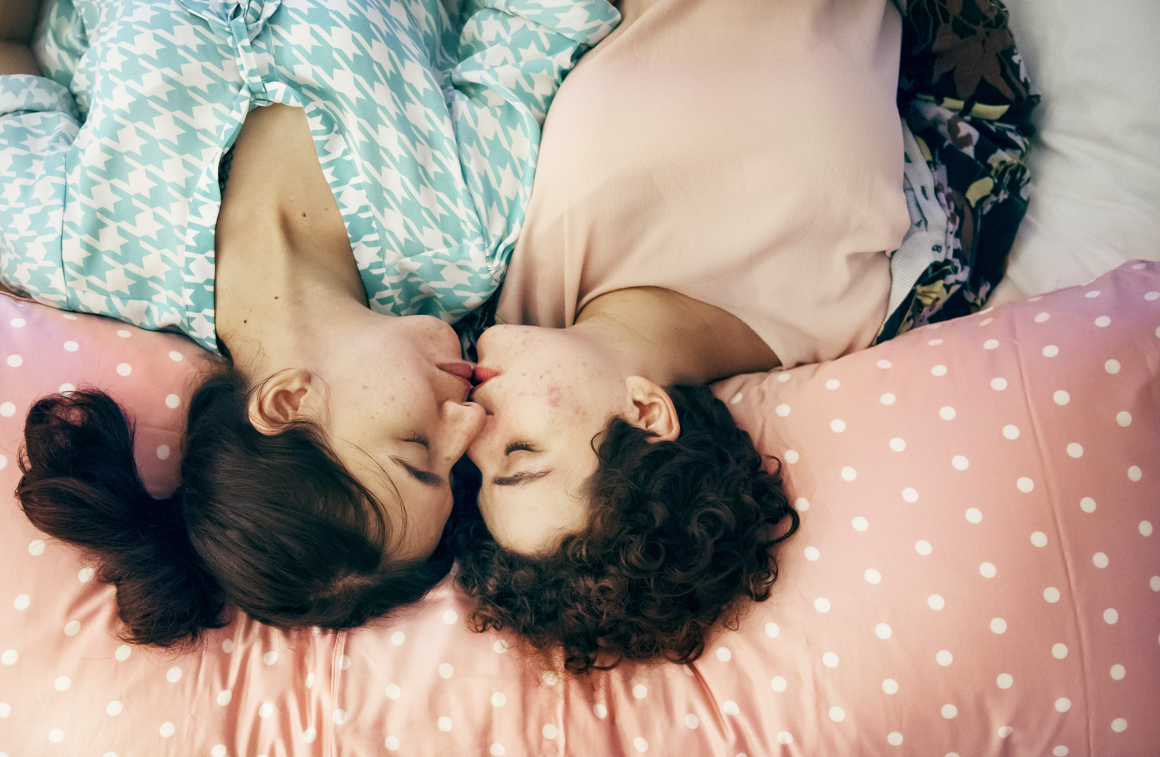 two women kissing while sleeping