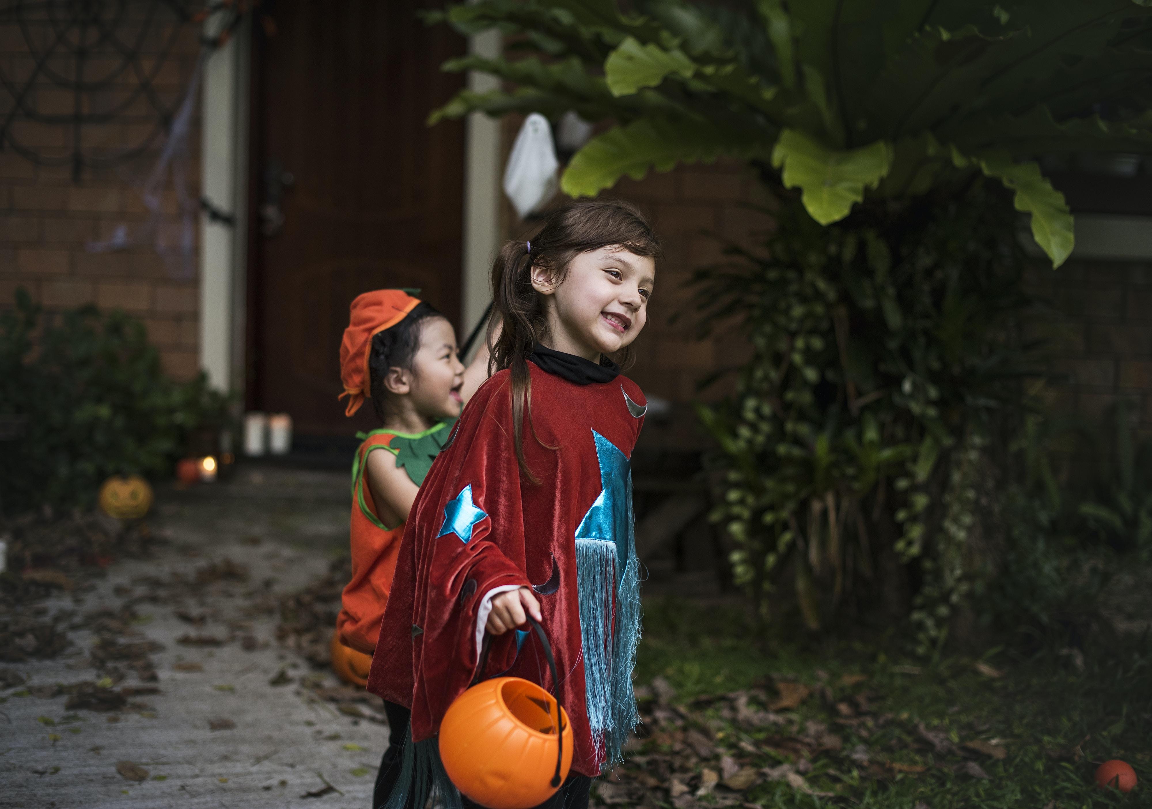girl holding Jack-o-lantern basket smiling