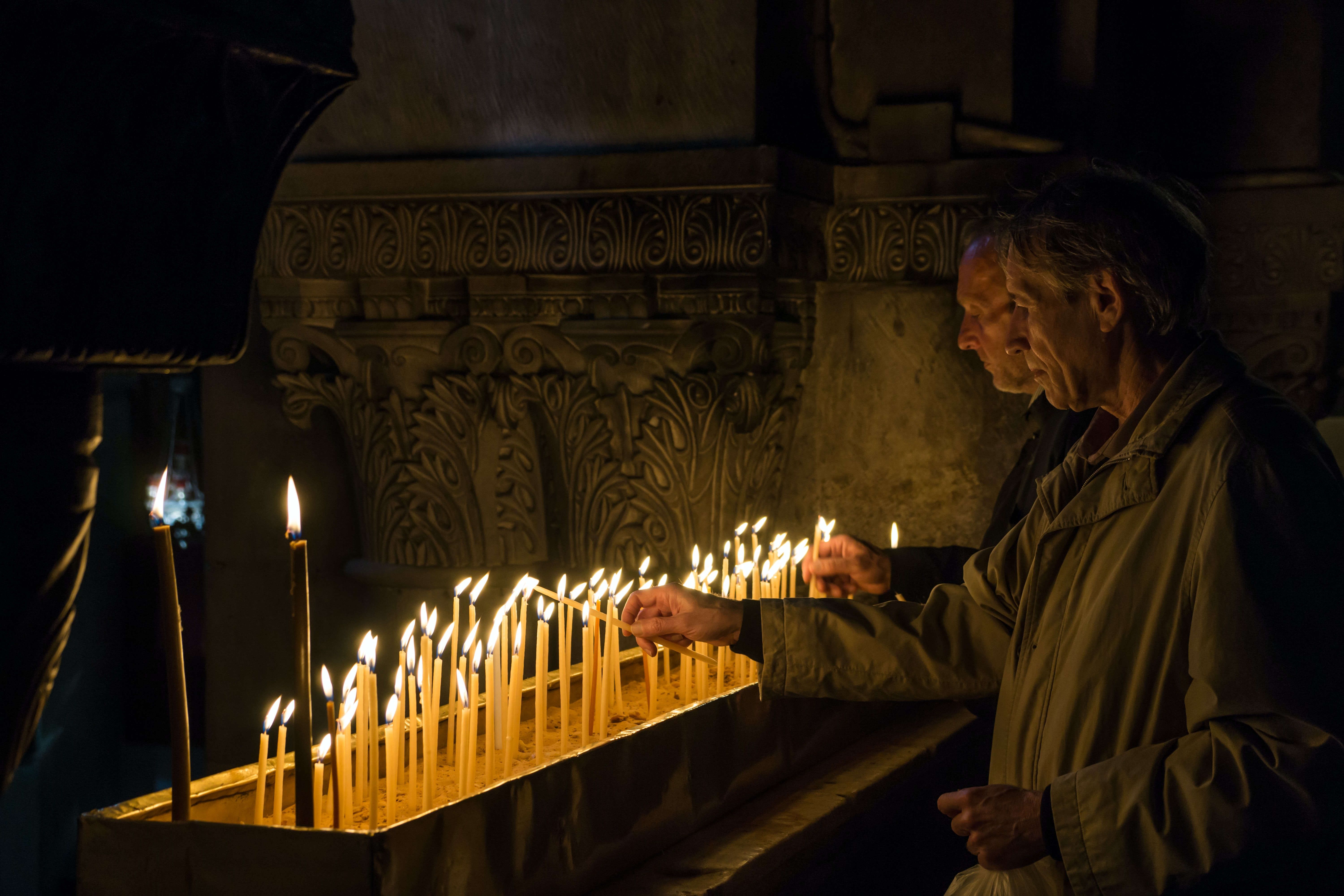 priest lighting up candles