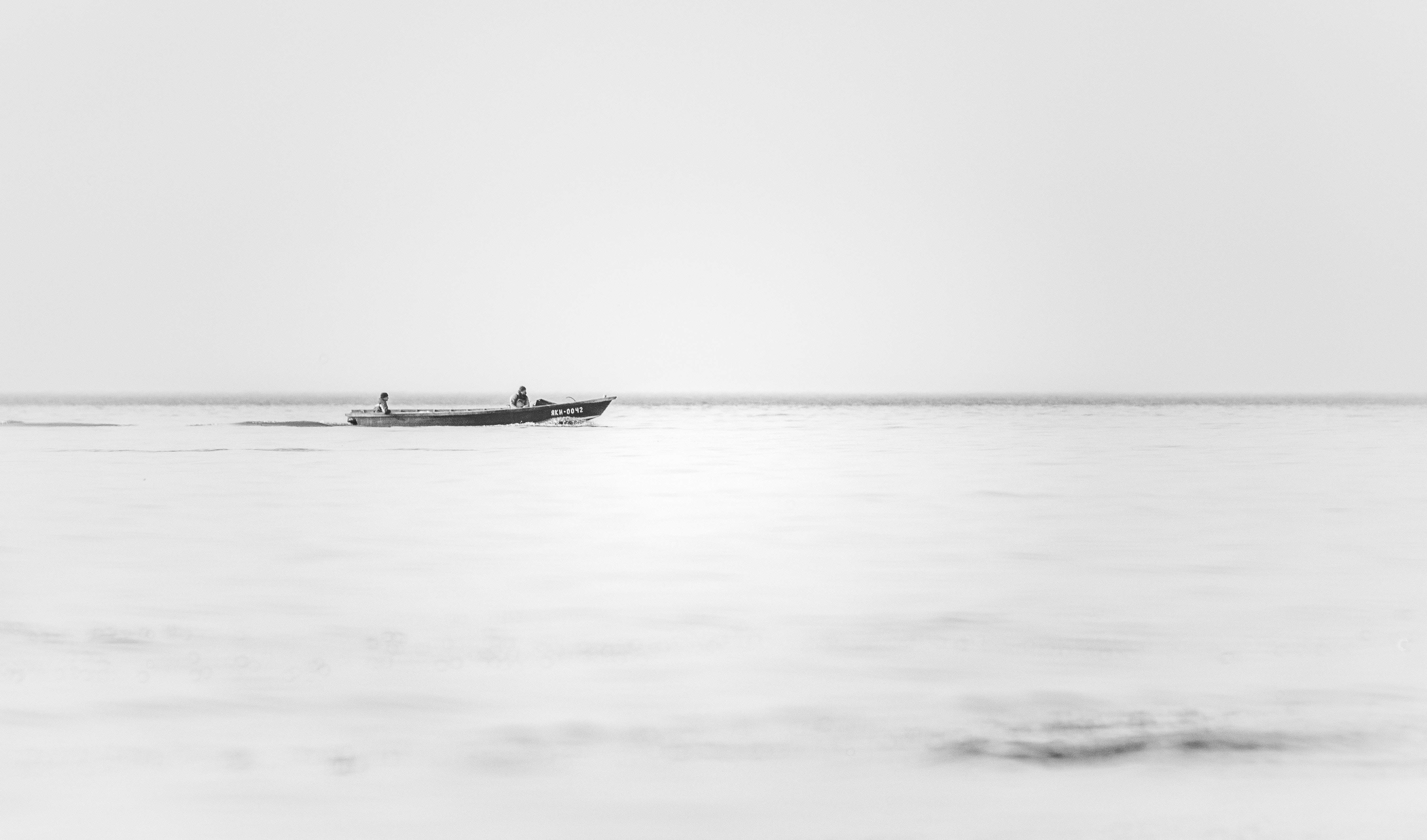 grayscale photography of boat on body of water