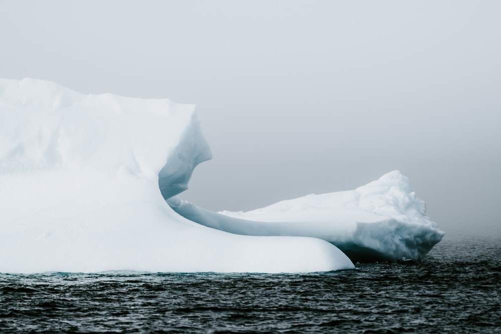 iceberg on sea under dark cloud