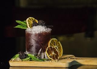 glass of fruit drink beside slice lemons