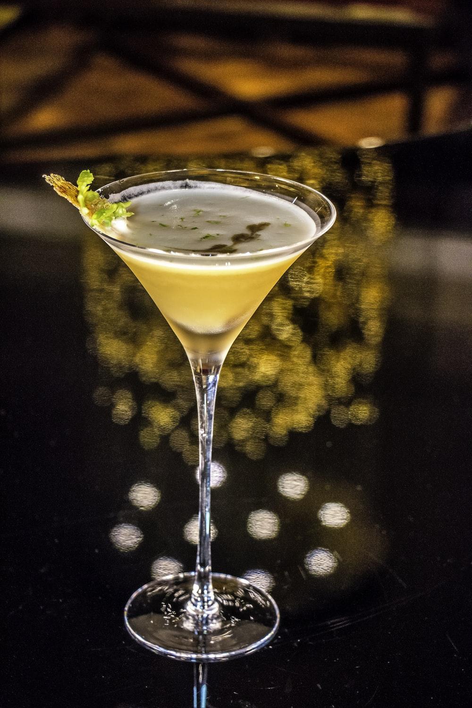yellow liquid on round glass martini