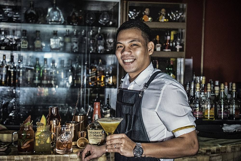 man smiling while holding martini glass filled with yellow liquid