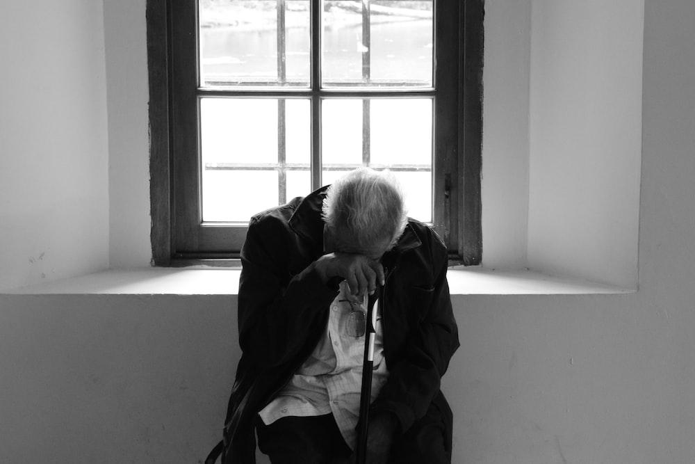 man sits on chair near window
