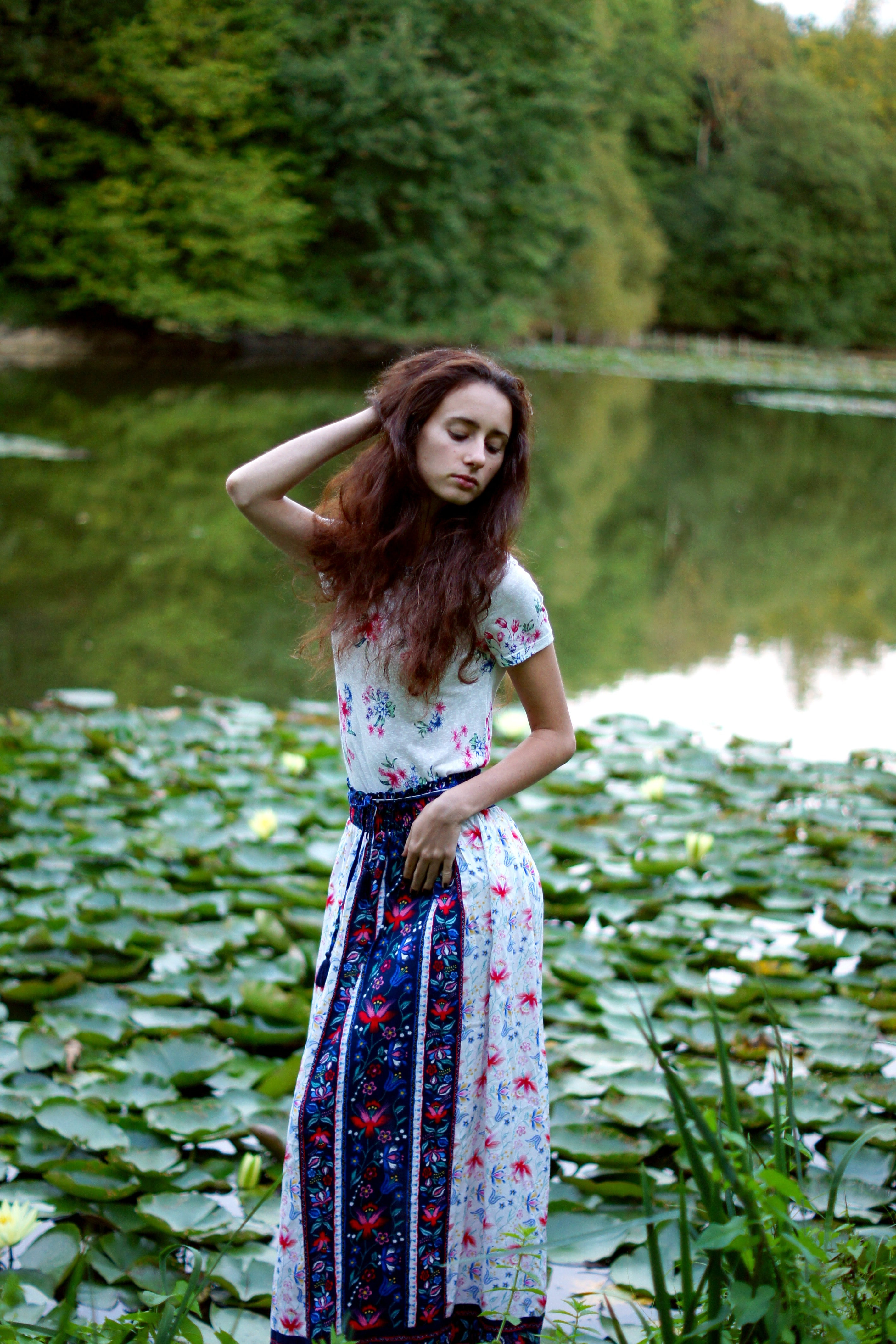 woman in white and blue floral dress standing in front of lake during daytime